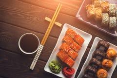 Różnorodni sety suszi rolki w ceramicznych talerzach na drewnianym stole, odgórny widok Fotografia Stock
