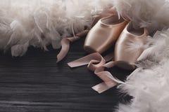 Różowi baletniczy pointe buty, piórko na czarnym drewnianym tle i Zdjęcia Royalty Free