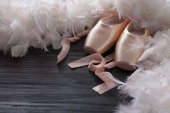Różowi baletniczy pointe buty, piórko na czarnym drewnianym tle i Fotografia Stock