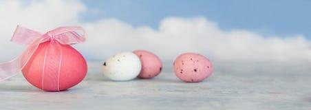 Różowi i biali Easter jajka, jeden z faborkiem przeciw rozmytemu b Obrazy Royalty Free
