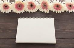 Różowy gerbera kwitnie i notatnik jest w drewnianym tle Obrazy Stock