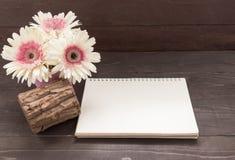 Różowy gerbera kwitnie i notatnik jest w drewnianym tle Zdjęcia Royalty Free