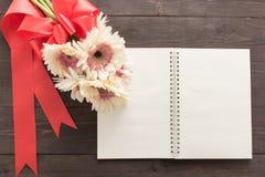 Różowy gerbera kwitnie i notatnik jest w drewnianym tle z faborkiem Obrazy Royalty Free