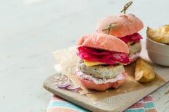 Różowy kurczaka grilla hamburger na drewnianym tle Obraz Royalty Free