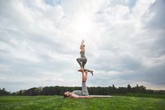 Równowag ćwiczenia Zdrowy i potomstwo dobiera się robić akrobatyczny joga w naturze Silnego mężczyzny lying on the beach na równo fotografia royalty free