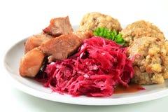Rôti de porc avec les boulettes tyroliennes et le kraut rouge image libre de droits