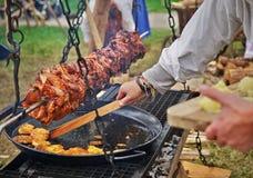 Rôti de viande au-dessus d'un gril, style médiéval photos stock