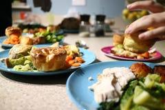 Rôtissez les dîners prêts à servir tandis qu'une main vole un pud de Yorkshire photos libres de droits