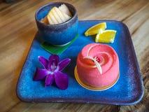 Röd älgkaka med orkidén och frukter i thailändsk stilgarnering på disk och på den wood tabellen Arkivbilder