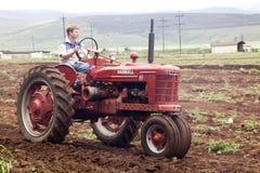 Röd återställd tappningtraktor som plöjer det jordbruks- fältet Arkivfoton