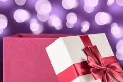 Röd öppnad gåvaask med pilbåge- och lilabakgrund med bokeh fotografering för bildbyråer