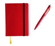 Röd anteckningsbok med pennan Fotografering för Bildbyråer