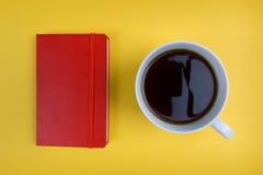 Röd anteckningsbok- och kaffekopp på ljus gul bakgrund royaltyfria bilder