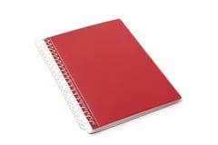 Röd anteckningsbok på vitbakgrund Arkivbilder