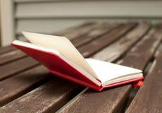 Röd anteckningsbok som är öppen på trätabellen Fotografering för Bildbyråer
