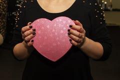 Röd ask i form av hjärtor i händerna av, gåva arkivfoto