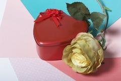 Röd ask med en gåva Gjort i formen av en hjärta arkivfoton