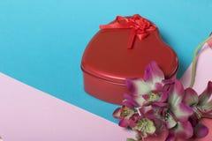 Röd ask med en gåva Gjort i formen av en hjärta arkivfoto