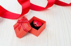 Röd ask med en vigselring Royaltyfri Foto