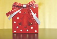 Röd ask med stearinljuset för tabelljulgarnering med den vita och röda pilbågen royaltyfria foton