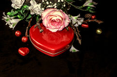 Röd askhjärta med choklader och bukett från vita blommor Arkivbilder