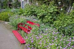 Röd bänk i blommor Arkivbilder