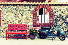 Röd bänk med blommor och motorcykeln Fotografering för Bildbyråer
