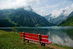 Röd bänk nära sjön med en bergsikt royaltyfria bilder