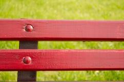 Röd bänk på det gröna gräset Arkivbilder