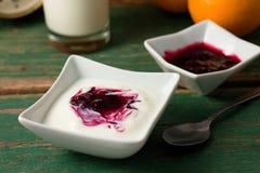 Röd bärfrukt i den vita yoghurten som förläggas med bunken på den gröna tabellen arkivbilder