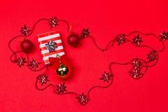 Röd bakgrund för jul med gåvan och garnering Royaltyfri Fotografi
