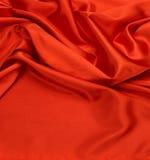 Röd bakgrund för siden- tyg Arkivfoto