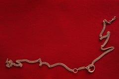 Röd bakgrund med den guld- kedjan Fotografering för Bildbyråer