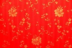 Röd bakgrund med guld- blommor Royaltyfria Foton