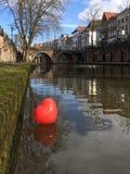 Röd ballong som svävar på den gamla kanalen av Utrecht Arkivbild