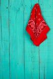 Röd bandana som hänger på tom antik dörr för krickablåttträ Royaltyfria Foton
