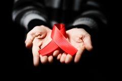 Röd bandmedvetenhet på den mänskliga handen för kvinnan åldrades vit bakgrund: Fotografering för Bildbyråer