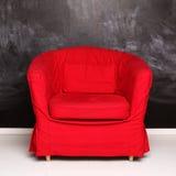 Röd begreppsmässig fåtölj på abstrakt svart tavlabakgrund Royaltyfria Bilder