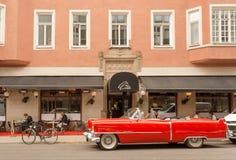 Röd bil för Cadillac cabriolet i parkerat förgånget hotell för tappning stil med avslappnande turister royaltyfria foton
