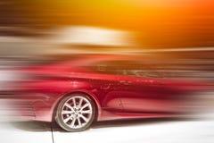 Röd bil i rörelsen Royaltyfri Bild