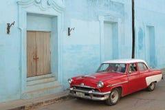 Röd bil och blåa väggar Arkivfoton