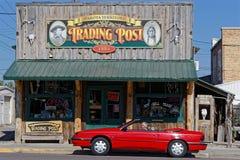 Röd bil och den handla stolpen i Custer arkivbilder