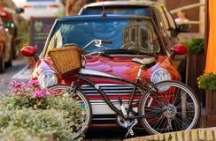 Röd bil och en cykel med en korg av vinrankor royaltyfri bild