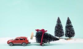 Röd bil och släp som bär en julgran Arkivbilder