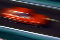 Röd bil på hastighet Fotografering för Bildbyråer