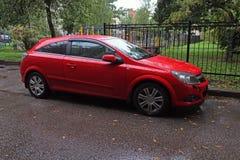 Röd bil som parkeras i borggården efter regn arkivfoton