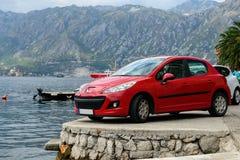 Röd bil som parkeras på steninvallningen av fjärden av Kotor Montenegro royaltyfria bilder
