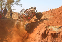 Röd bil som ramping ut ur den branta dugouten, tre inställda hjul Royaltyfria Bilder