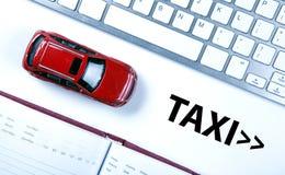 Röd bilmodell nära tangentbordet i begreppet av att kalla en taxi Royaltyfri Fotografi