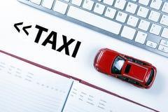 Röd bilmodell nära tangentbordet i begreppet av att kalla en taxi Arkivfoto